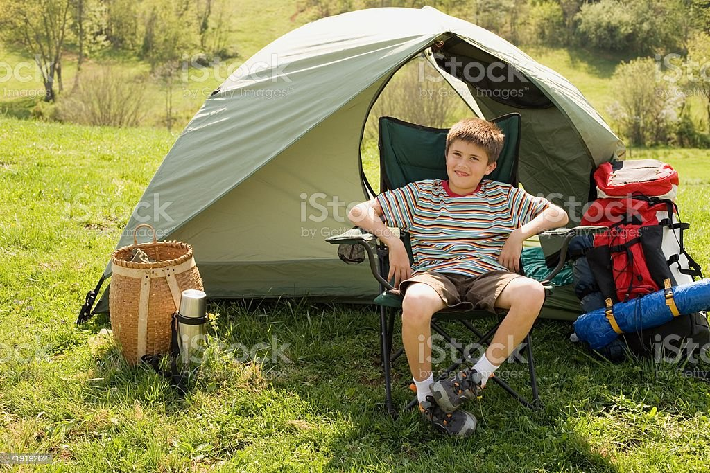 Boy sitting in front of tent royalty-free stock photo