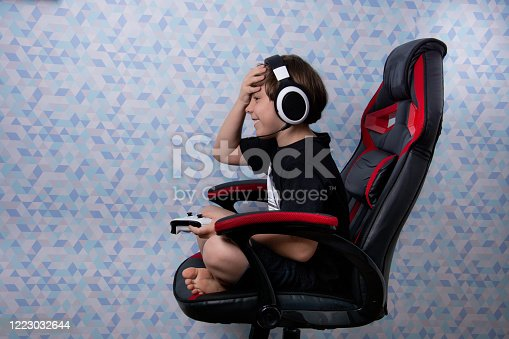 boy sitting in gamer chair with headset and video game control