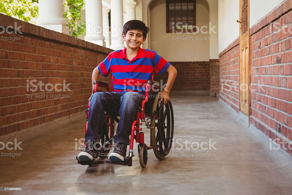 Boy sitting in wheelchair at school corridor stock photo