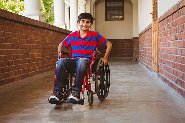 Boy sitting in wheelchair at school corridor stock photo