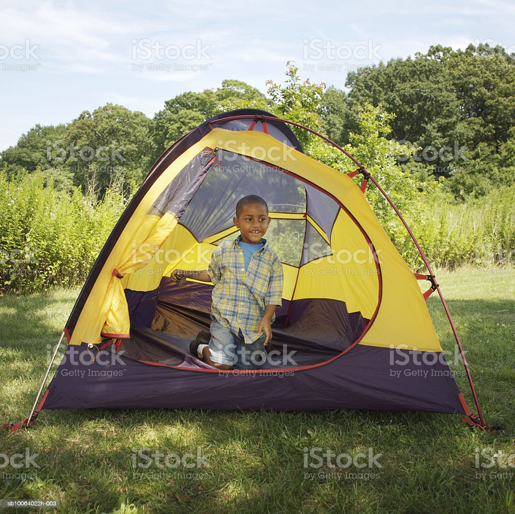 Boy (4-5) sitting inside tent, smiling photo libre de droits