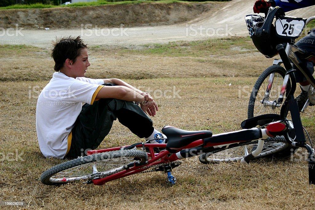 Boy sitting next to bmx bike royalty-free stock photo