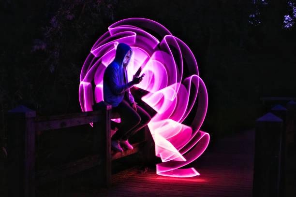 男孩手裡拿著智慧手機坐在橋上 - 霓虹色 個照片及圖片檔