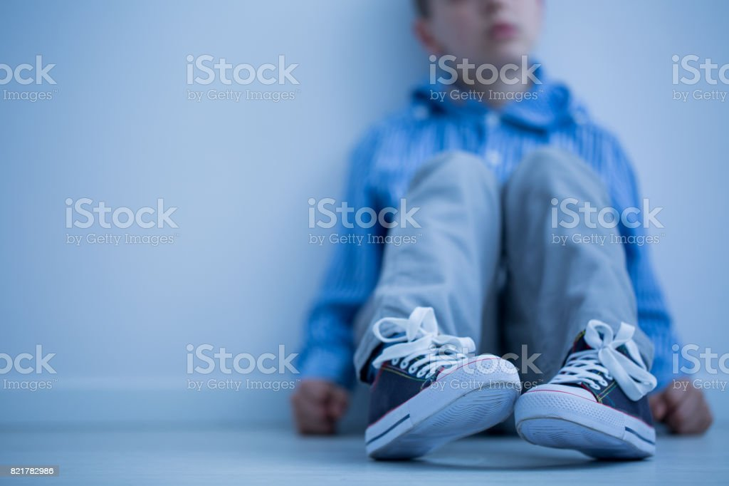 Boy sitting on a floor stock photo
