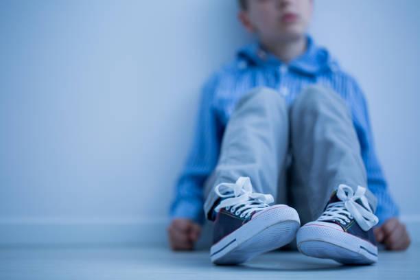 Jeune garçon assis sur un sol - Photo