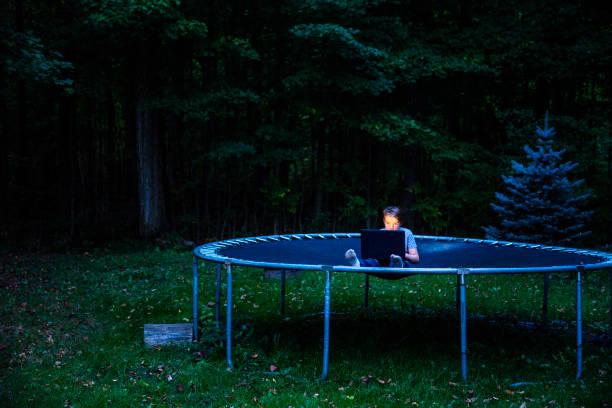 junge sitzt auf einem trampolin in der dämmerung mit ein laptop - gartentrampolin stock-fotos und bilder