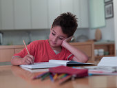 Boy sitting on chair and doing homework