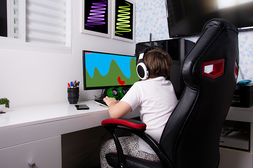 boy sitting on gamer chair playing on computer
