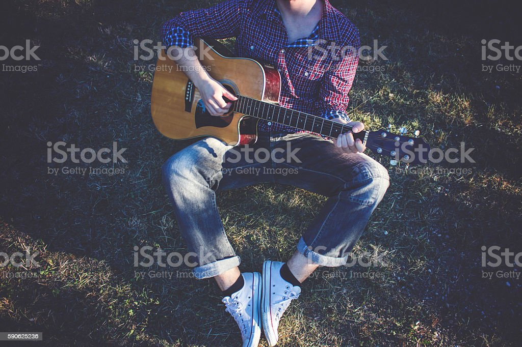 Boy sitting on grass and playing guitar stock photo