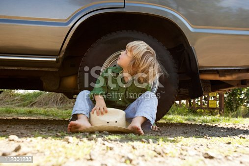 112301234 istock photo Boy sitting on ground with a cowboy hat, looking up at car 112301233