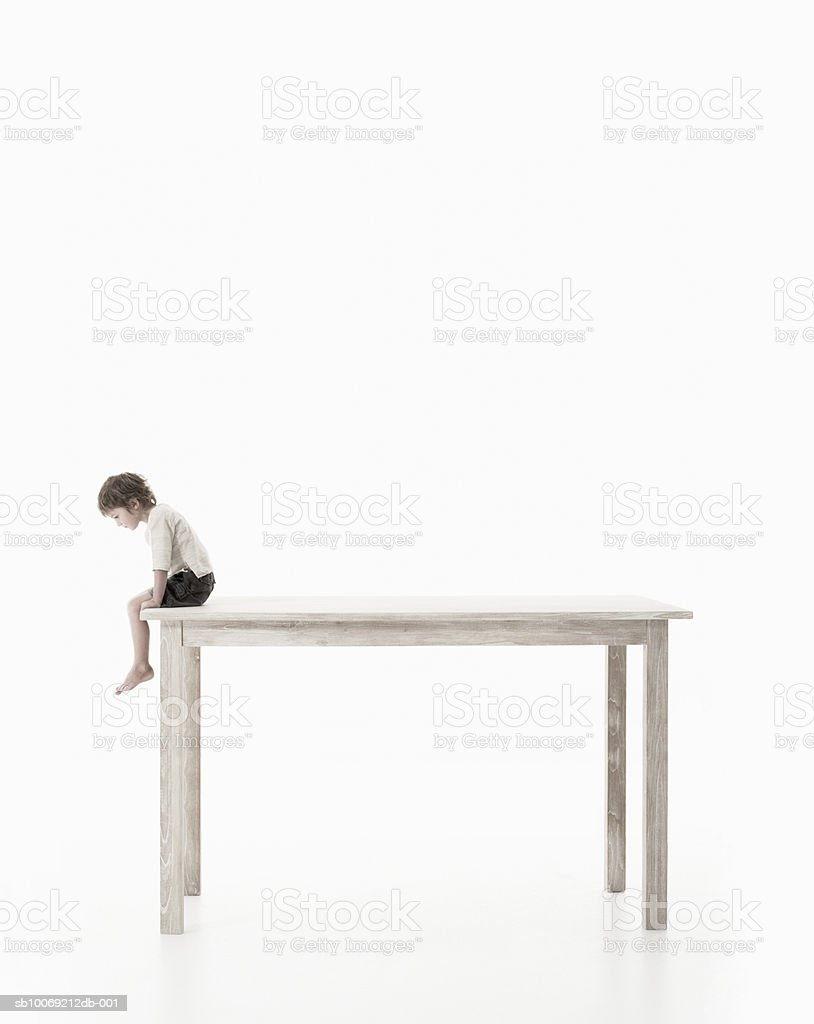 Boy (4-5 years) sitting on oversized table, studio shot, side view royalty-free stock photo