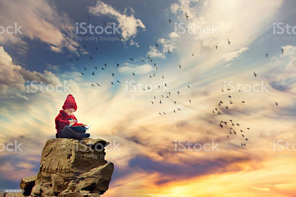 Boy, sitting on rock in sky, birds flying around him stock photo