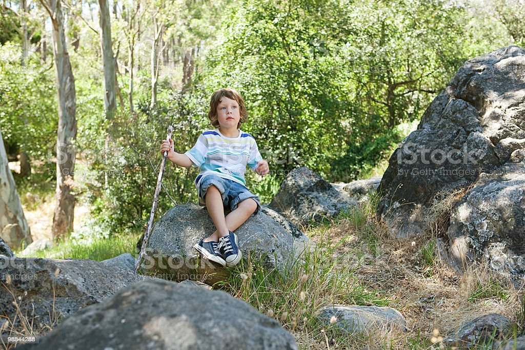 Boy sitting on rock royalty free stockfoto