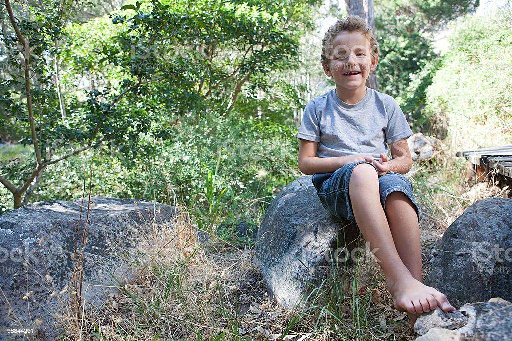 Niño sentado en rock foto de stock libre de derechos