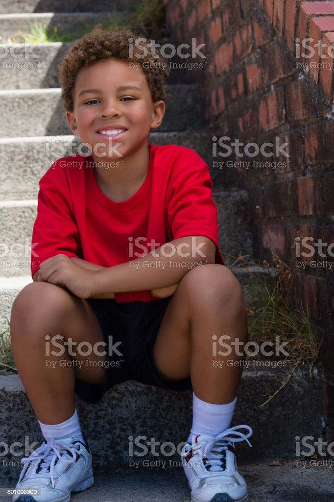 Boy sitting on staircase in the boot camp on a sunny day stock photo
