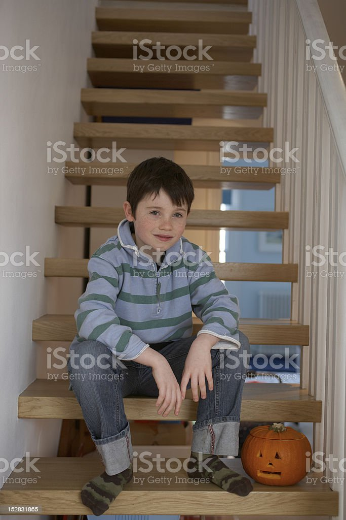 Boy sitting on steps with carved pumpkin stock photo