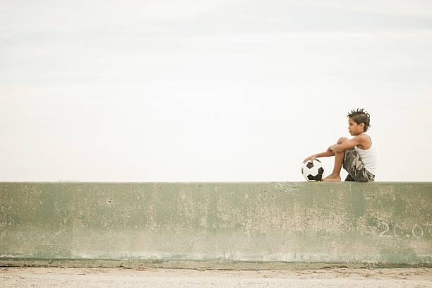 Junge sitzt auf Wand mit football – Foto