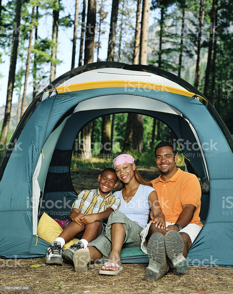 Boy (10-12) sitting with parents in tent, portrait royalty-free stock photo