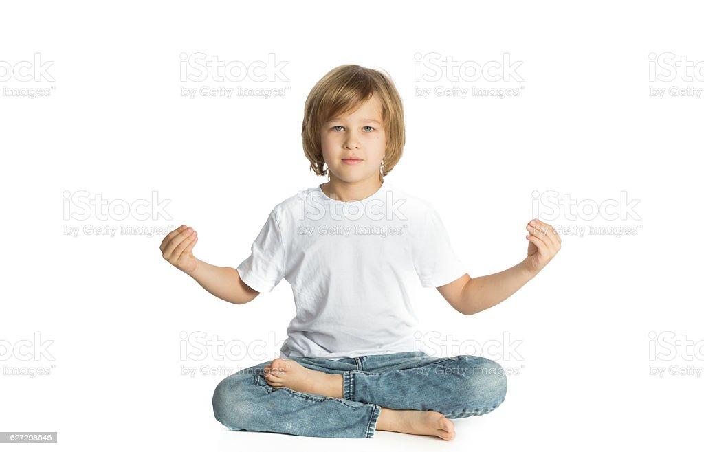 Boy sitting. Yoga. Lotus Position. stock photo