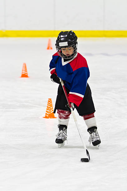 Boy skating with the puck at ice hockey practice stock photo