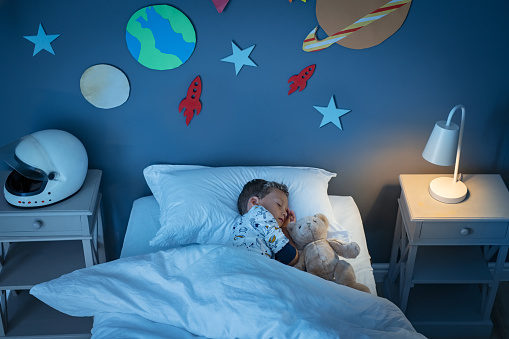 High angle view of little boy dreaming of becoming an astronaut while sleeping with teddy bear in space decorated room. Top view of dreamer child sleeping on bed with solar system and planet decoration during the night. Cute kid with astronaut helmet on side table and the light on.