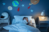 istock Boy sleeping and dreaming a future in the space 1256104370