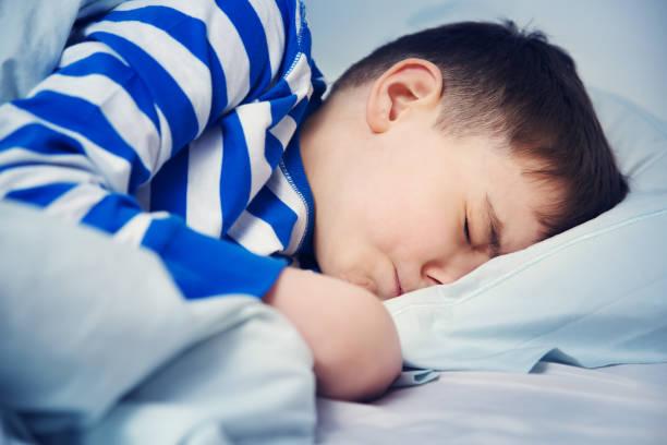 jungen schlafen im bett im pyjama - bett für jungs stock-fotos und bilder