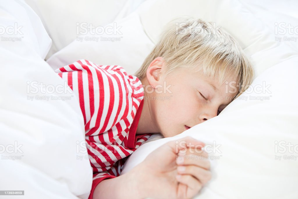Boy sleeping in bed with crisp white sheets royalty-free stock photo