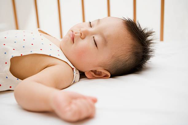 Boy sleeping in crib stock photo