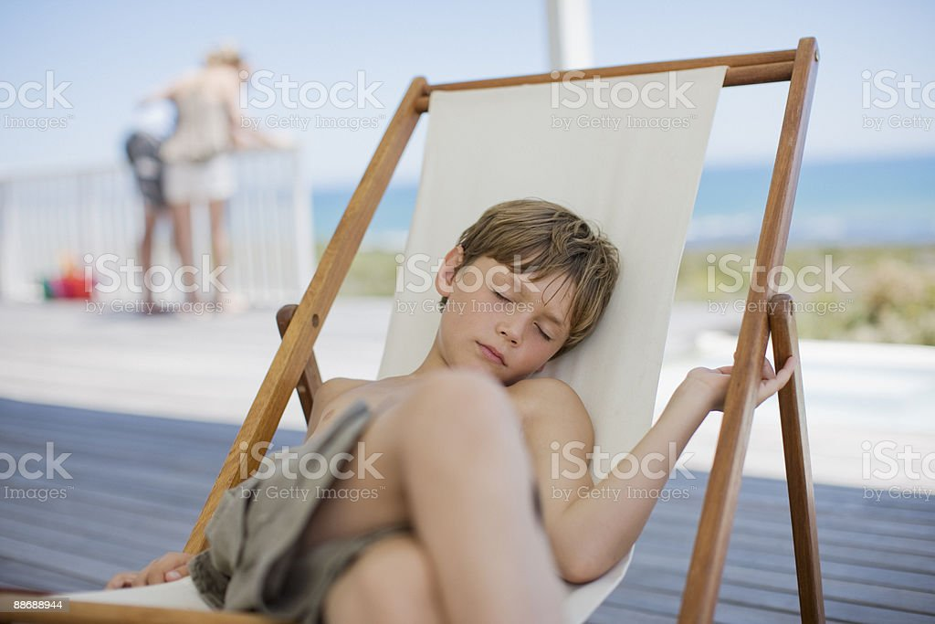 Boy sleeping in lounge chair on deck royalty-free stock photo