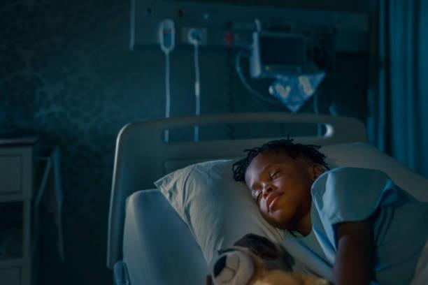 jungen schlafen mit stofftier auf krankenstation - bett für jungs stock-fotos und bilder