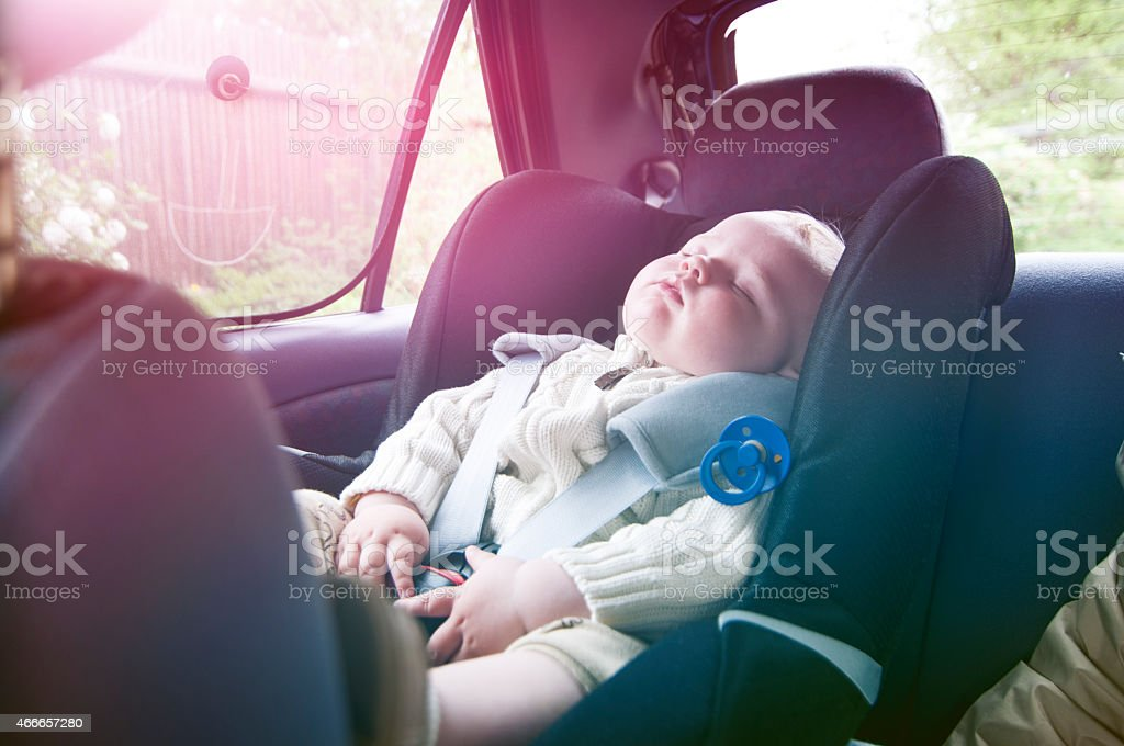 Boy sleeps in baby car seat on a road trip stock photo