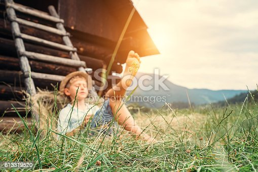 Boy sleeps in grass under hayloft in summer afternoon