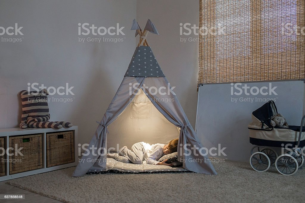 boy sleeps in the teepee stock photo