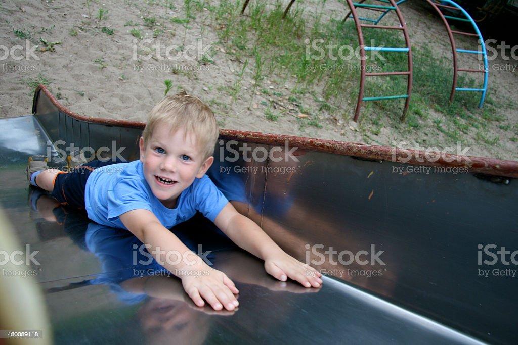 boy slides on the stomach stock photo