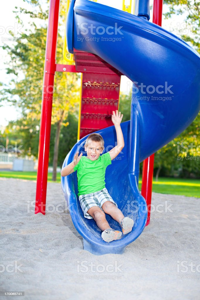 Boy sliding down a slide at playground stock photo
