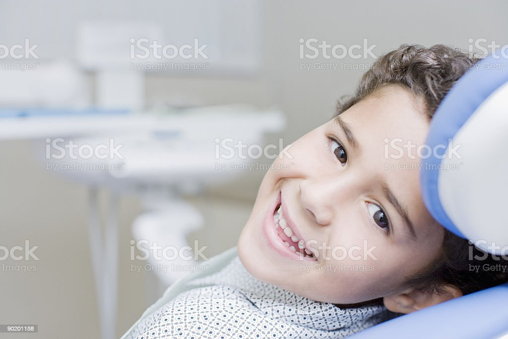 Boy smiling and sitting in dentists chair stock photo