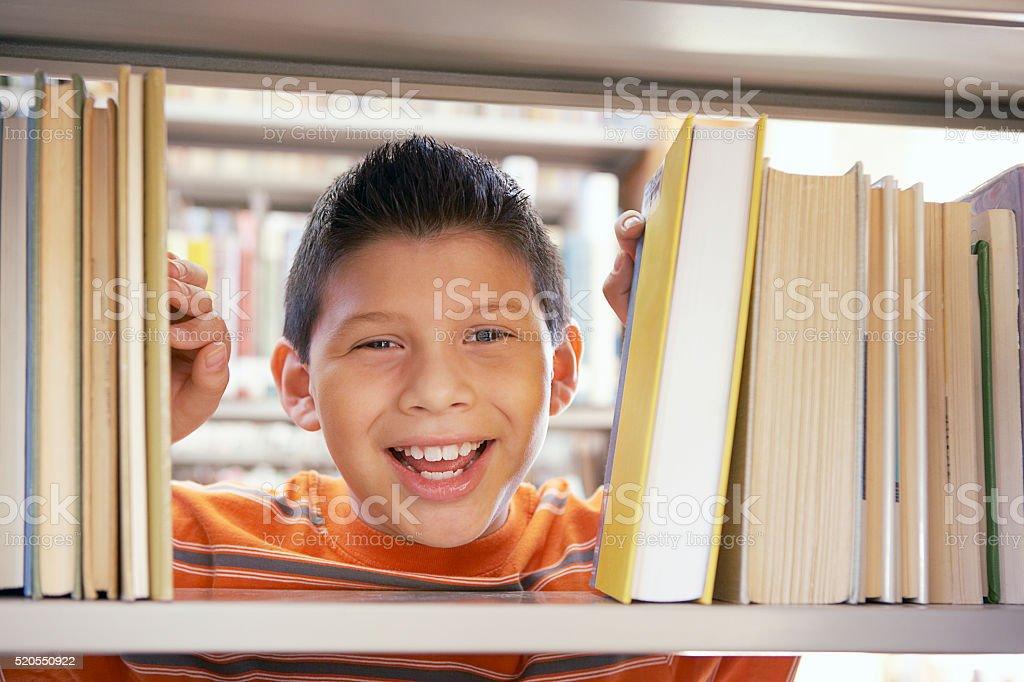 Boy smiling between books stock photo