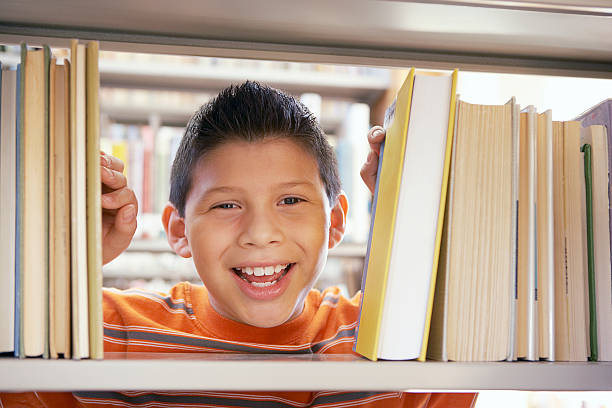 boy smiling between books - boy looking out window stock pictures, royalty-free photos & images