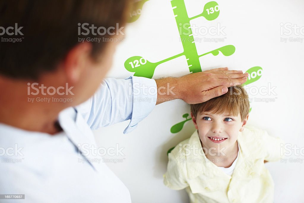Boy smiling while measuring his height stock photo