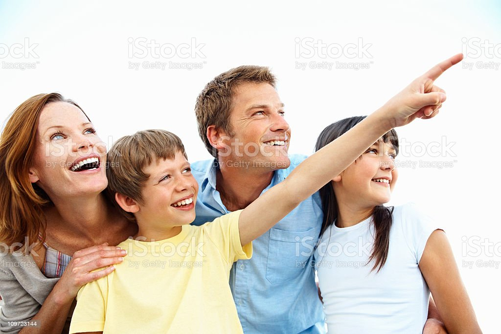 Boy smiling with his family and pointing away stock photo