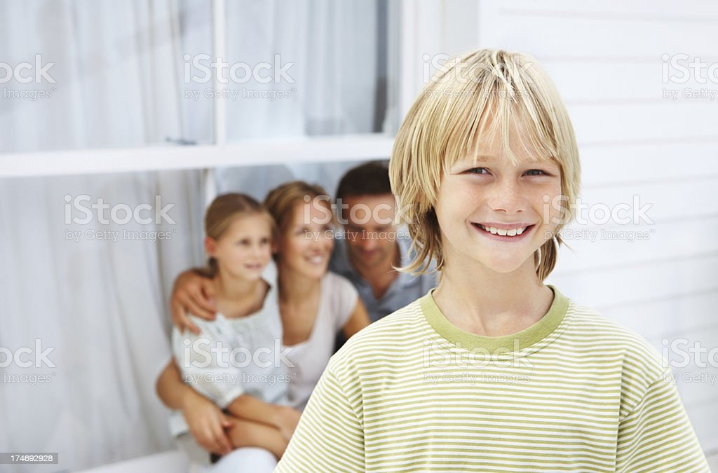 Boy smiling with parents in the background royalty-free stock photo