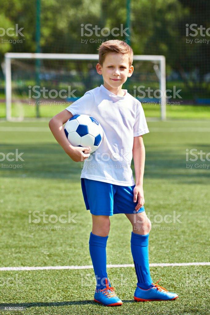 Boy soccer football player with ball on an green grass stock photo
