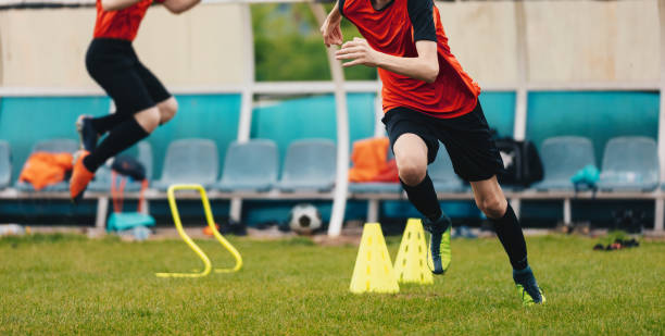 Boy Soccer Player In Training. Boys Running Between Cones amd Jumping During Practice in Field on Sunny Day. Young Soccer Players at Speed and Agility Practice Session Boy Soccer Player In Training. Boys Running Between Cones amd Jumping During Practice in Field on Sunny Day. Young Soccer Players at Speed and Agility Practice Session between stock pictures, royalty-free photos & images