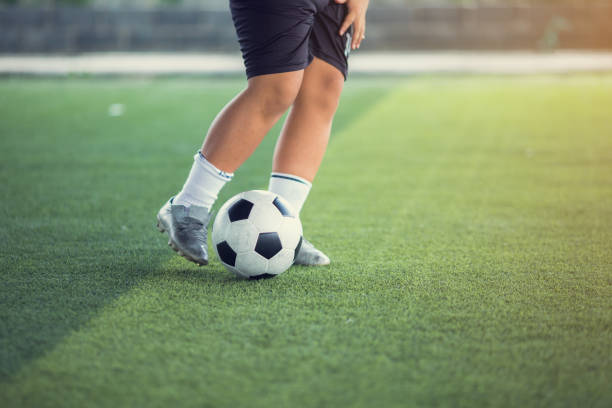 Boy soccer player shoot ball on green artificial turf to goal. Boy soccer player training. Boy soccer player shoot ball on green artificial turf to goal. Boy soccer player training. Asian player in football academy. training equipment stock pictures, royalty-free photos & images