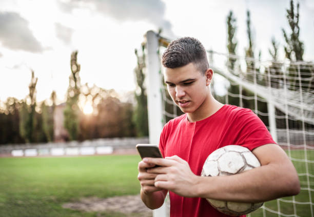 Boy soccer player using cellphone