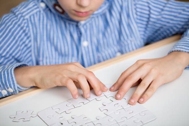 Boy solving a white puzzle stock photo