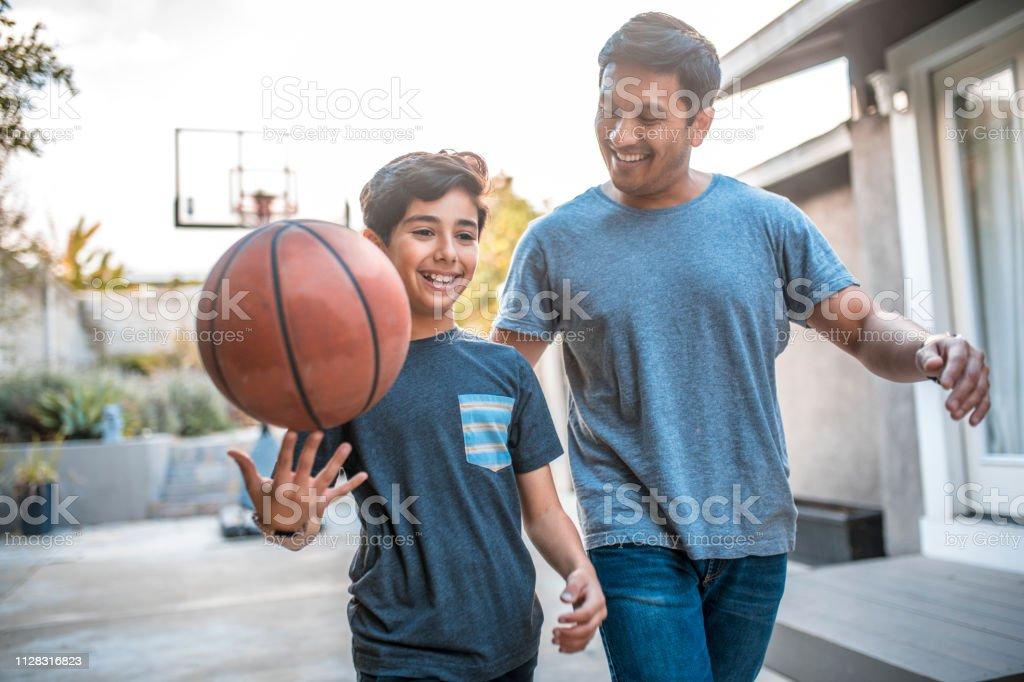 Jongen spinnen basketbal tijdens het wandelen door vader - Royalty-free 30-39 jaar Stockfoto
