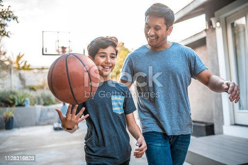 Happy boy spinning basketball while walking by father. Mid adult man and child are smiling in backyard. They are wearing casuals during weekend.