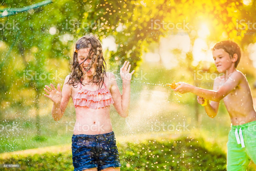 Boy splashing girl with water gun, sunny summer garden stock photo
